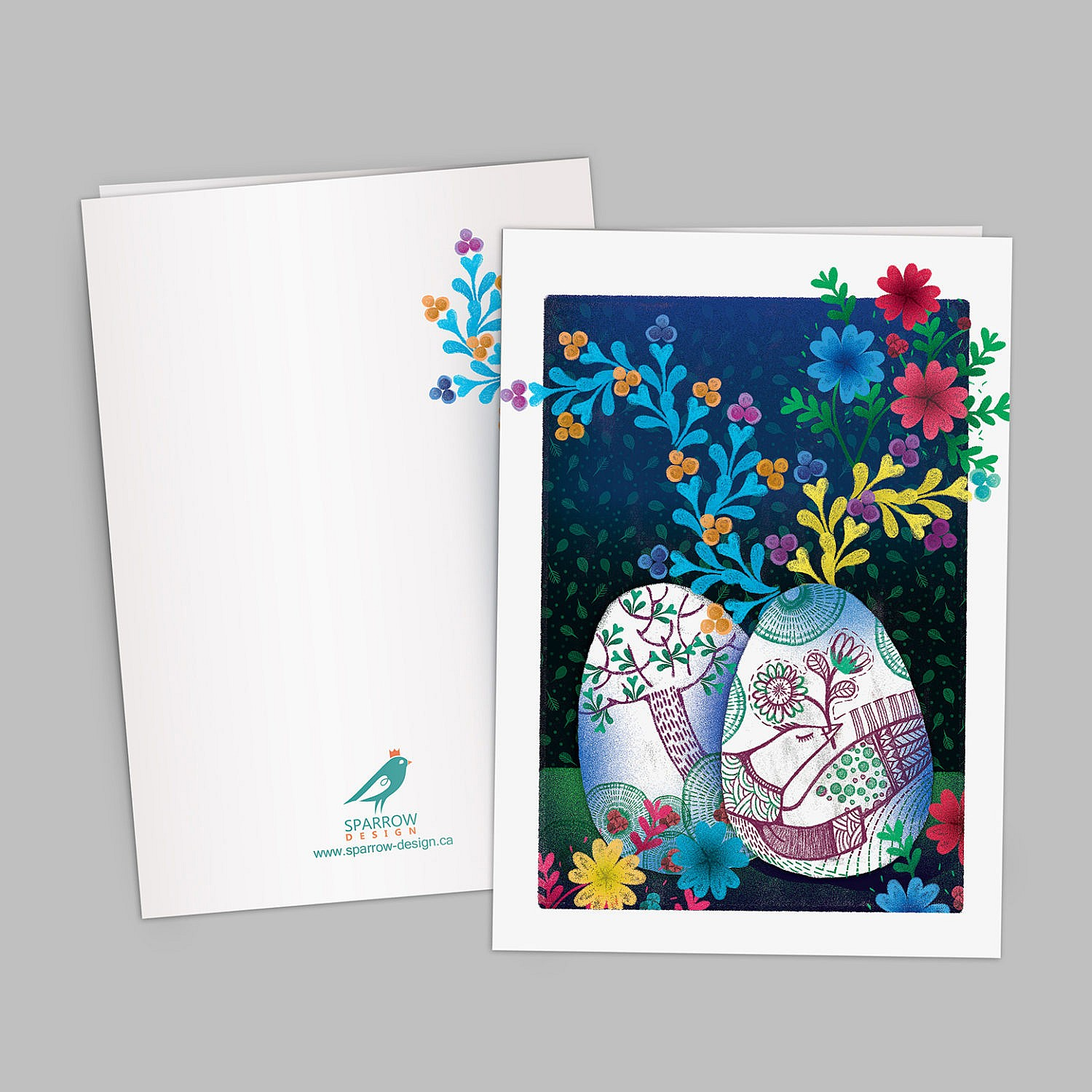 The image include an illustrated greeting card which is designed to celebrate Spring. The image shows two beautiful painted eggs one is showing a bird and the second one is showing a tree which is has pink blossom. In the background there are colorful flowers. The background is blue and green.