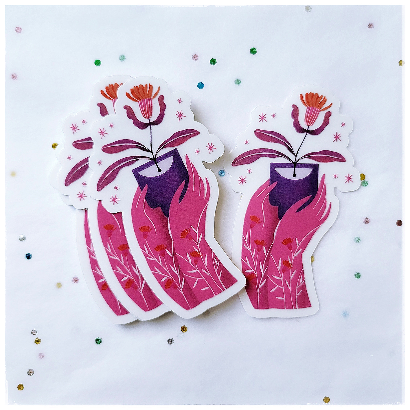 Clear vinyl sticker that showing two pink hands that are offering a red flower in a lovely manner. Both hands are covered with white and red tiny flowers. This sticker is water and weather proof.